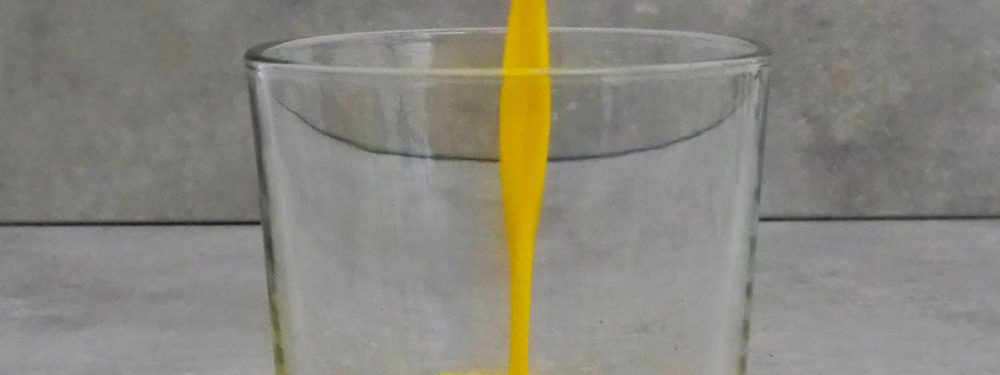 Goldene Milch fließt zentral in ein kleines Glas