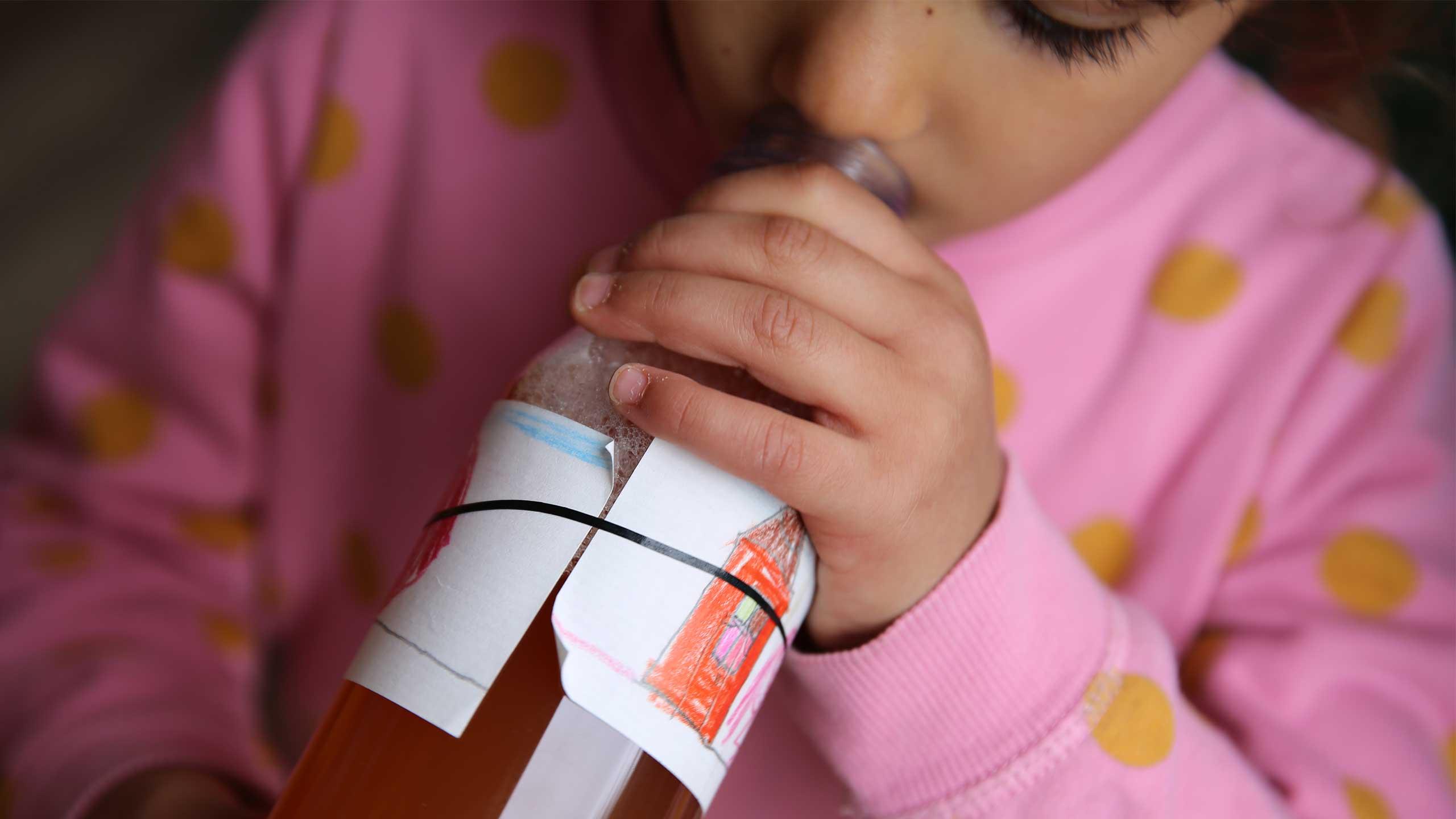 Ein Kind probiert bei MILK. Mahlzeit den ersten Schluck Apfelsaft