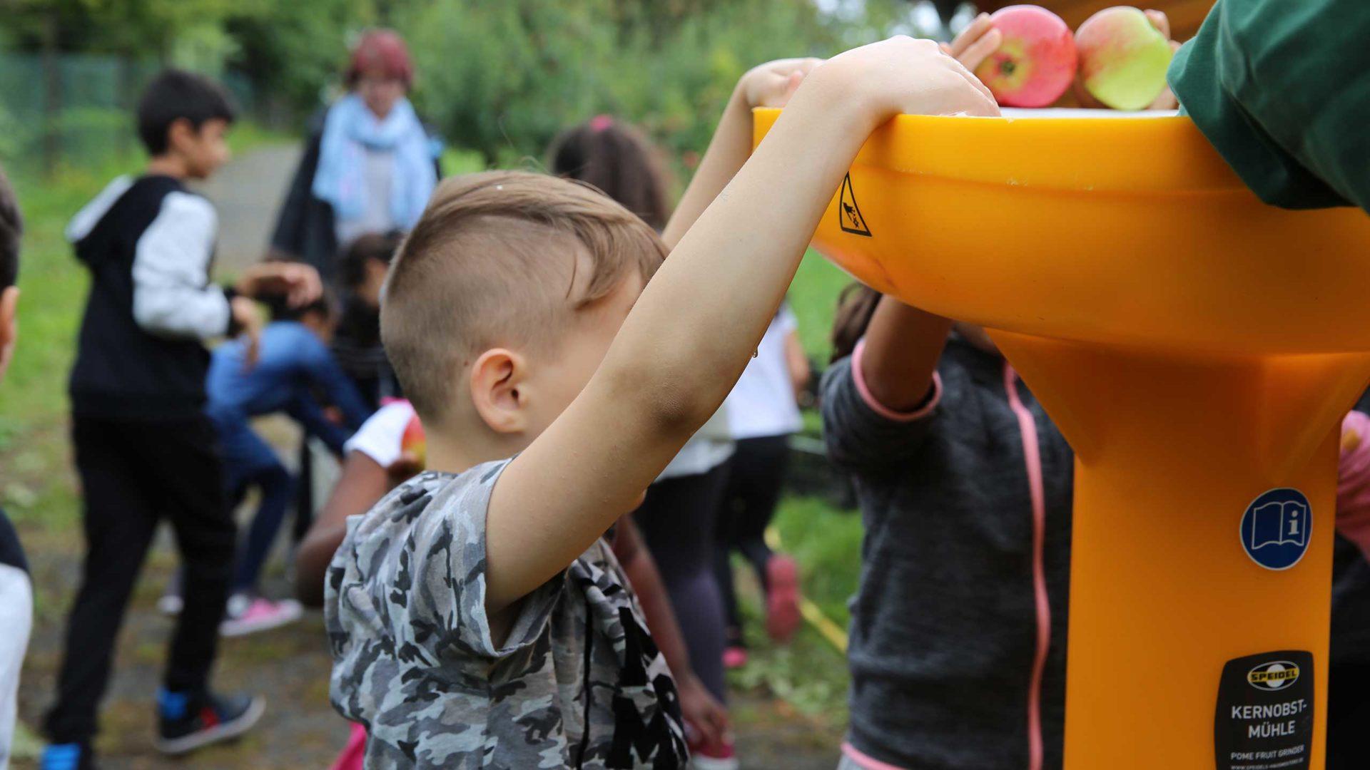 Milk Aktion Mahlzeit auf dem Apfelhof. Oben kommen die Äpfel rein unten kommt der Saft raus.