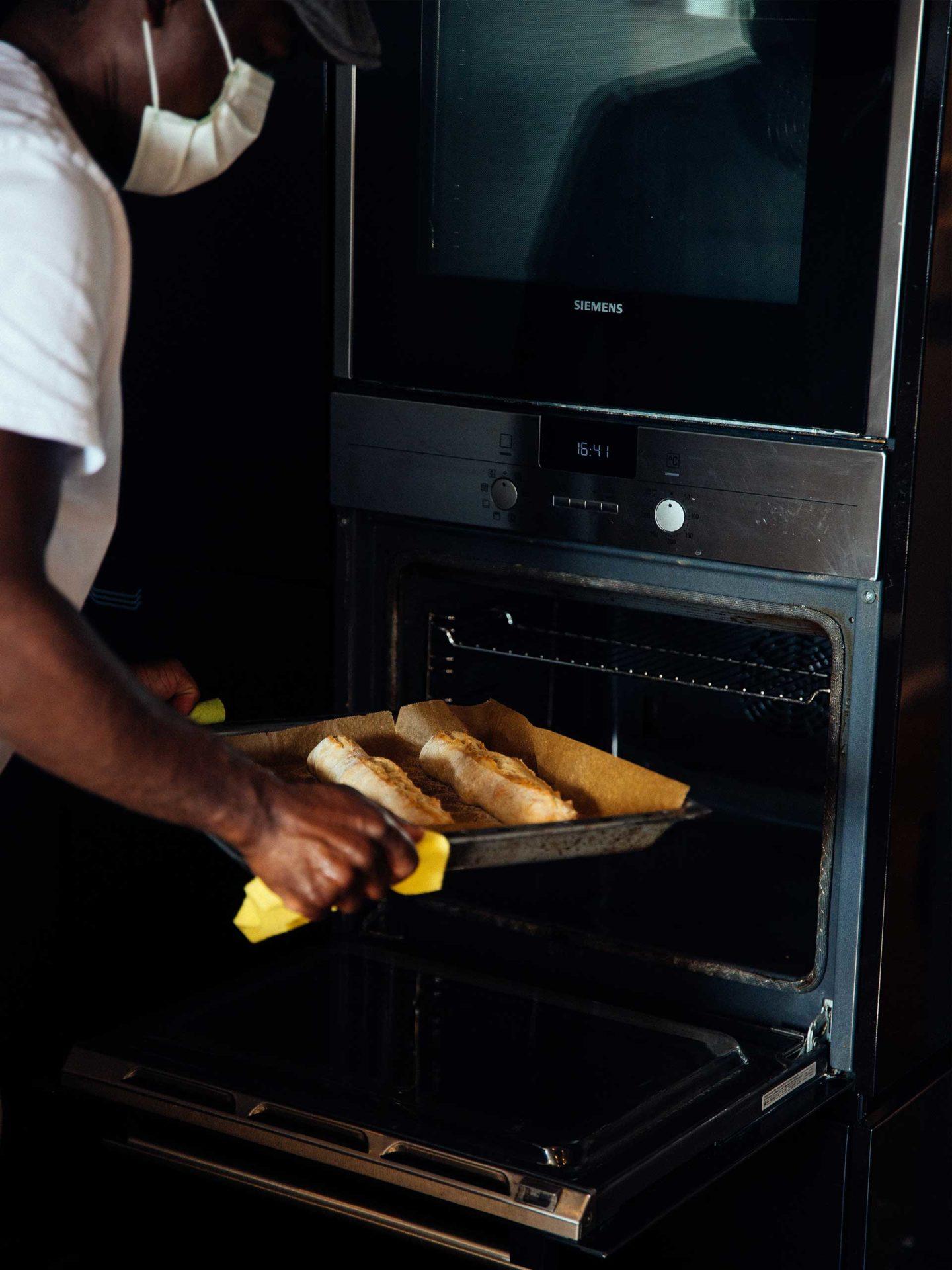 Aktion Mahlzeit. Daph holt die fertigen Baguettes aus dem Ofen.