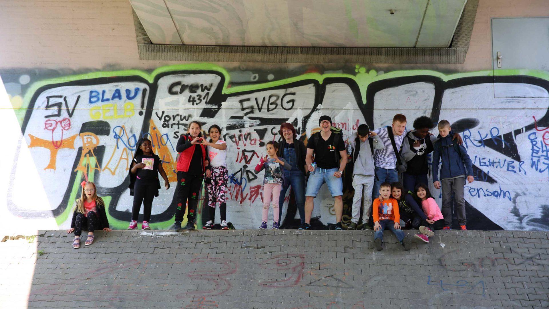 Aktion Mahlzeit bei den Imkern. Gruppenfoto vor einem Graffiti.