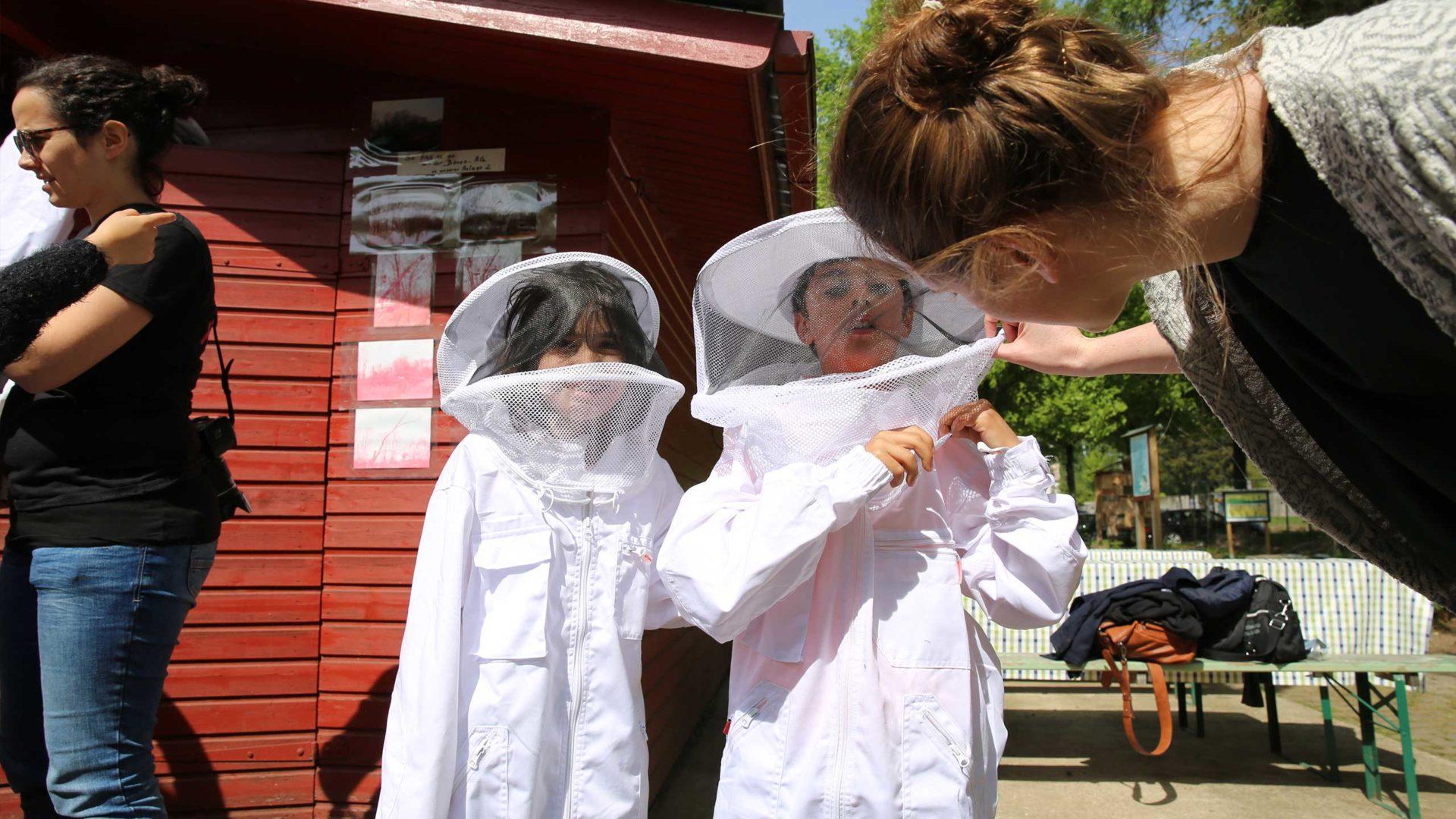 Aktion Mahlzeit bei den Imkern. Die Kinder dürfen in echte Imkeranzüge anziehen und kommen ganz nah an die Bienen heran. Anprobe der Anzüge. Ist auch sicher alles dicht?
