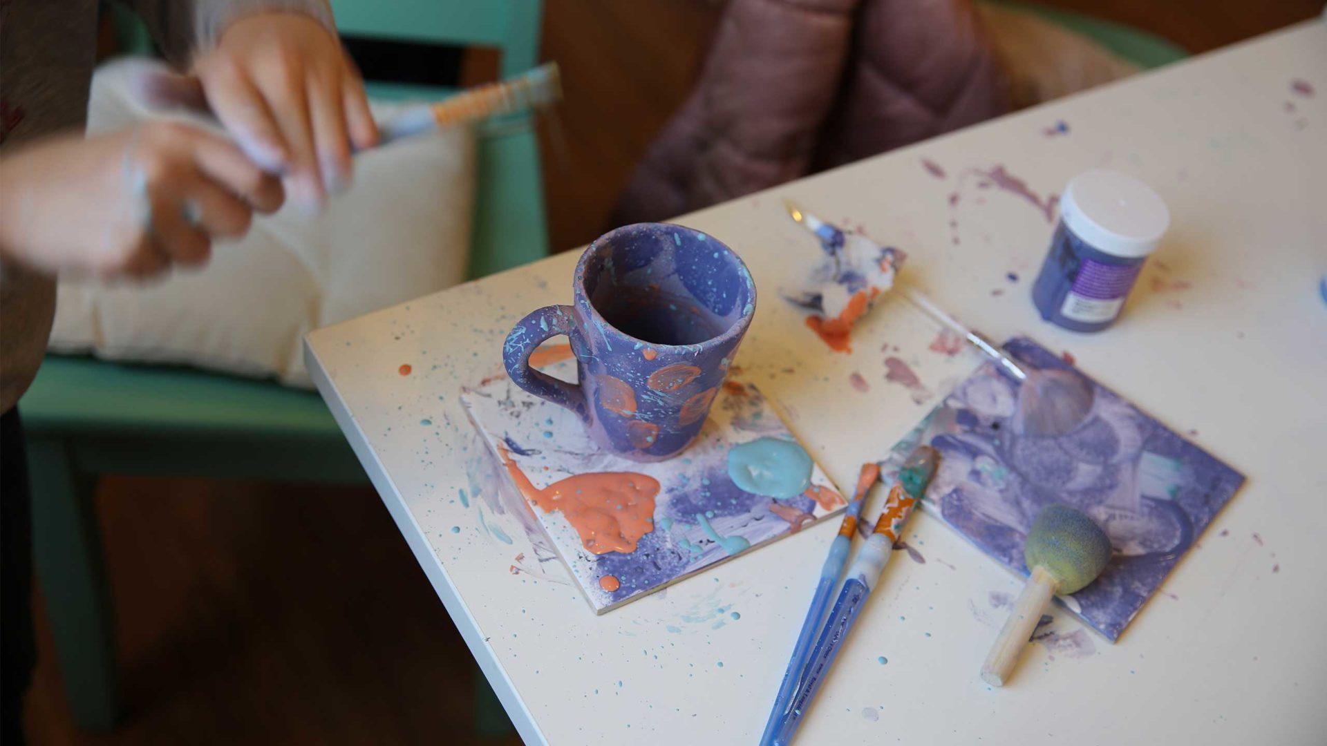 eine Tasse auf einem Tisch der Kreativwerkstatt mit Pinseln und Farbkleksen