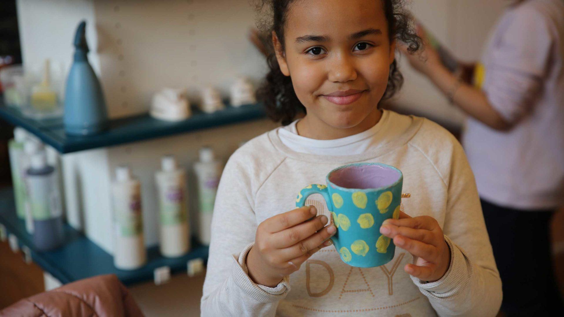 Ein Kind aus der Arche Frankfurt mit einer selbstgemachten Tasse in der Hand steht in der Kreativwerkstatt