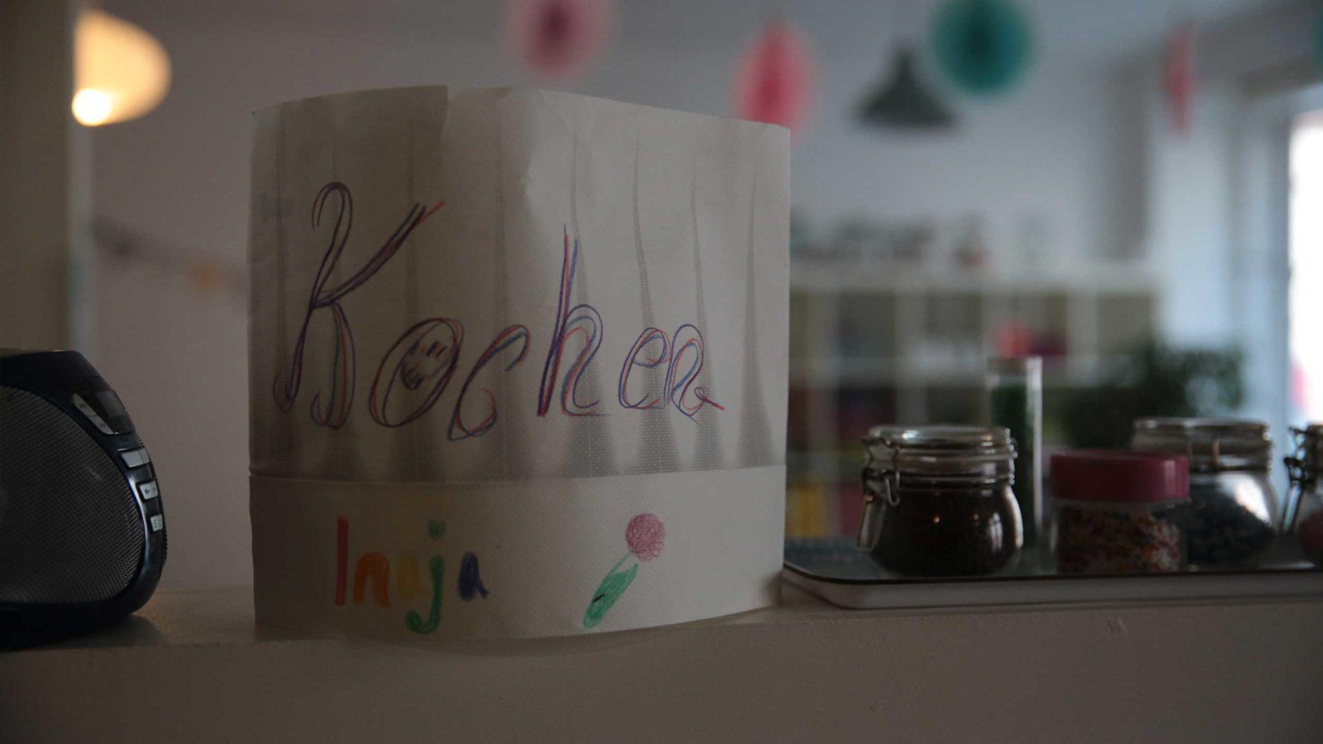 Aktion Mahlzeit. Die Kinder Haben ihre Namen auf die Kochmütze geschrieben.