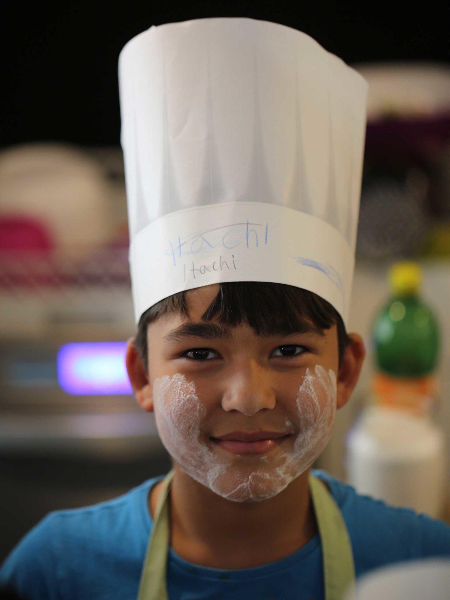 Aktion Mahlzeit. Der kleine Hachi ist fleißig beim Backen dabei gewesen. Sein Gesicht ist voll mit Mehl bedeckt.