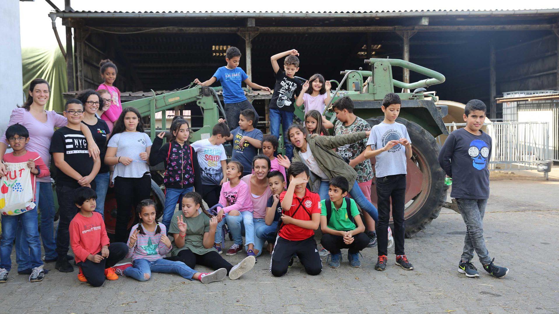 Aktion Mahlzeit auf dem Milchhof. Gruppenfoto auf einem Traktor.