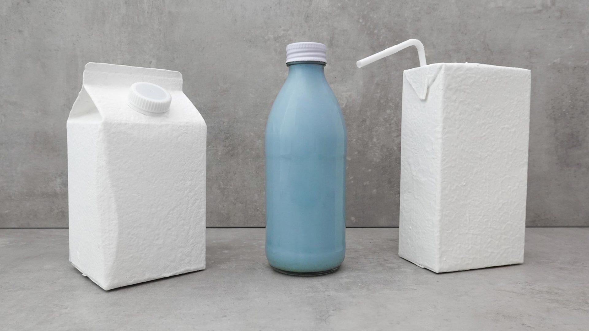 Zwei klassische weiße PET-Verpackungen mit einer blauen Glasflasche in der Mitte