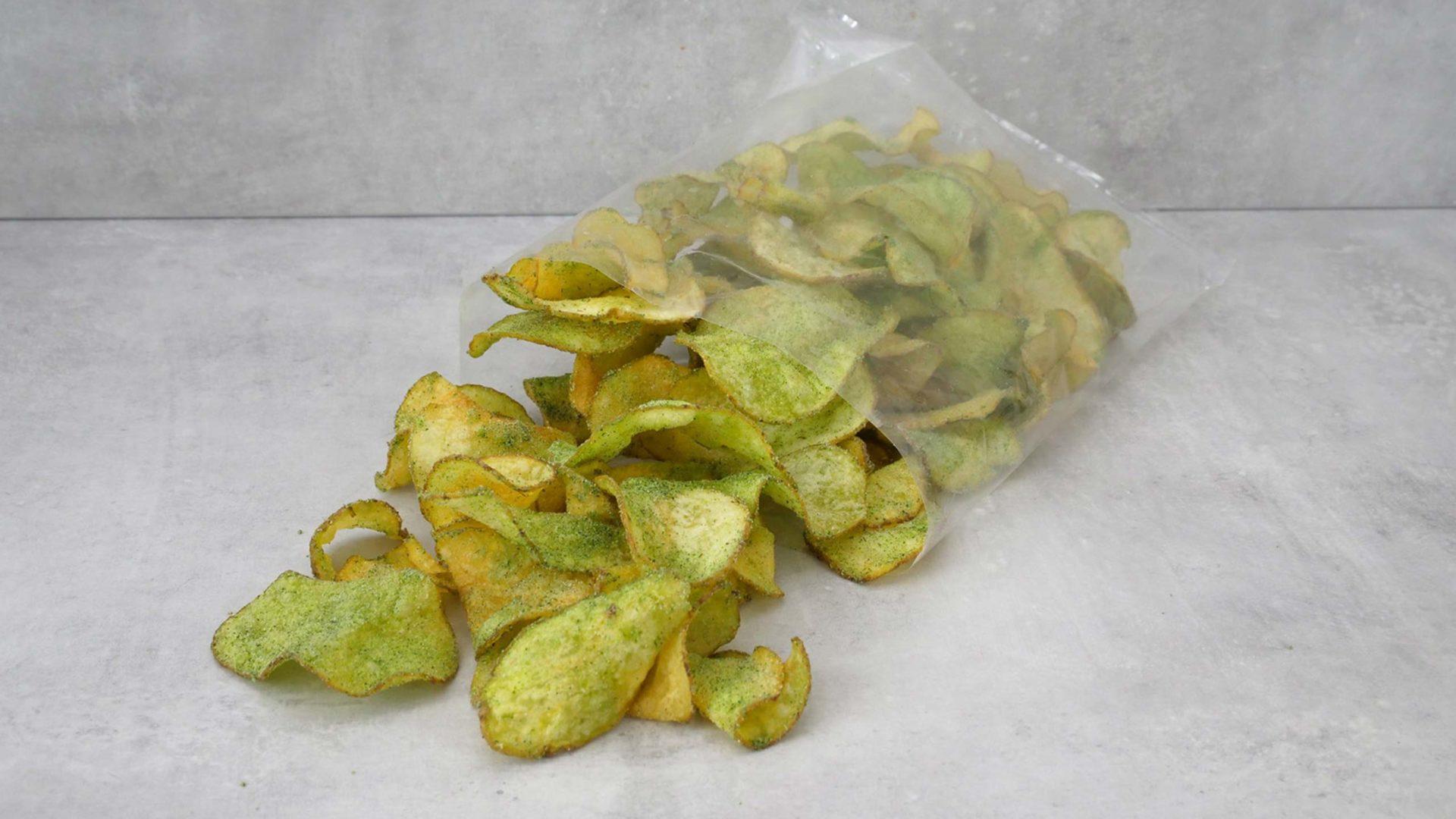 Grün bestäubte Chips in offener, durchsichtiger Tüte