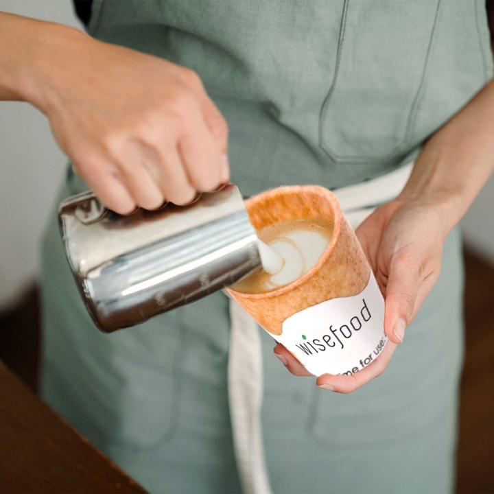 Aufgeschäumte Milch fließt in einen ganz besonderen Kaffeebecher: Den essbaren von Wisefood.